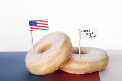Donuts with Happy 4th of July. Two Donuts with American Flag and a white Banner with Happy 4th of July, Isolated stock image