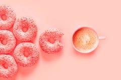 Donuts i filiżanka kawy w kolorze panton żywy koral, różowy tło zdjęcie royalty free