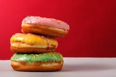 Donuts i mång--färgad glasyr som överst staplas av de på en röd bakgrund, kopieringsutrymme Bageri som annonserar begrepp fotografering för bildbyråer