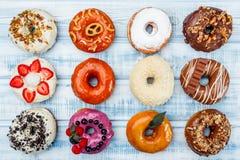 Donuts i sortiment, på gammal wood bakgrund Top beskådar Utrymme för text arkivfoton