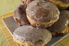 Donuts with icing. Traditional yeast donuts, deep-fried covered with icing, on a plate Royalty Free Stock Images