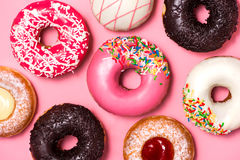 Donuts with icing on pastel pink background. Sweet donuts stock photos