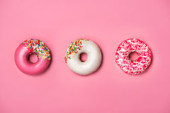 Donuts with icing on pastel pink background. Sweet donuts. Royalty Free Stock Images