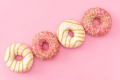 Donuts with icing on pastel pink background. Sweet donuts stock photography