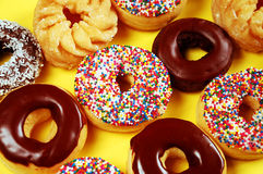 Donuts with icing and sprinkles. Assorted donuts with icing and sprinkles Royalty Free Stock Images