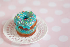 Donuts with icing sprinkles. Donuts with blue icing and color sprinkles in knitted saucer on pink background Royalty Free Stock Photo