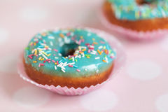 Donuts with icing sprinkles. Donuts with blue icing and color sprinkles on pink background Royalty Free Stock Image