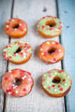 Donuts with icing sprinkles. Donuts with green and pink icing and color heart sprinkles on light wooden background Royalty Free Stock Photography