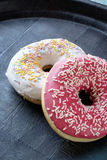 Donuts with icing an sprinkles portrait side Royalty Free Stock Photography
