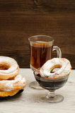 Donuts with icing sugar, a mug of tea and currant jam on a wooden background Royalty Free Stock Photography