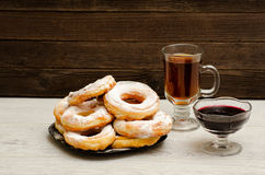 Donuts with icing sugar, a mug of tea and currant jam on a wooden background Stock Images