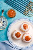 Donuts with jam on a plate and Hanukkah on a turquoise table. Vertical Stock Photography
