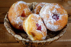 Donuts with jam in a wicker basket Stock Photos