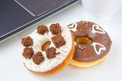Donuts laptop coffee Stock Images