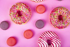 Donuts and macaroons on a pink background. Delicious desser. Delicious dessert stock images