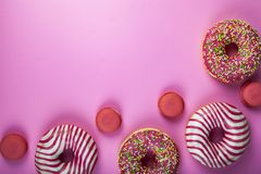 Donuts and macaroons on a pink background. Delicious desser. Delicious dessert royalty free stock image