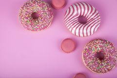 Donuts and macaroons on a pink background stock photography