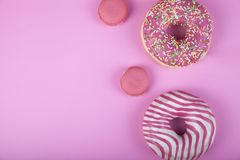 Donuts and macaroons on a pink background stock image