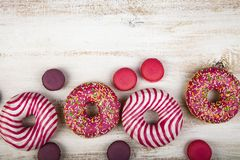 Donuts and macaroons on a wooden background stock photos