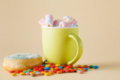 Donuts and marshmalow on cream color background Royalty Free Stock Photography