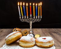 Donuts and a menorah for Hanukkah Stock Photos