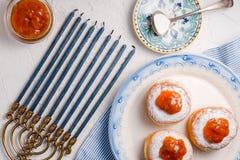 Donuts met abrikozenjam op een ceramische plaat en Chanoeka hoogste mening stock afbeeldingen