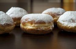 Donuts met poedersuiker tegen donkere achtergrond Stock Afbeeldingen