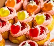 Donuts met slagroom en bovenste laagje met hart gevormde gelei wordt gevuld die stock foto's