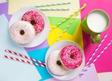 Donuts met suikerglazuur en melk op pastelkleur kleurrijke achtergrond Zoet royalty-vrije stock foto