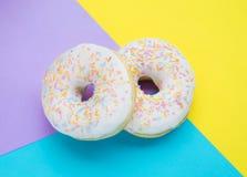 Donuts met suikerglazuur op pastelkleur kleurrijke achtergrond royalty-vrije stock afbeeldingen