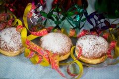 Donuts mit Papierschlangen für Karneval Lizenzfreie Stockfotos
