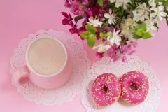 Donuts and mocha latte coffee. Romantic style. Refreshment. Time. Donuts and mocha latte coffee with  spring flowers on a pink background. Romantic style Stock Images