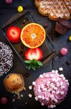 Donuts and muffins with fruit on black stone background. royalty free stock image