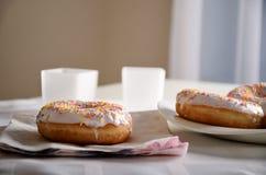 Donuts och disk på tabellen horisontal Arkivbilder