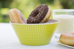 Donuts och exponeringsglas av mjölkar i trädgård Arkivfoton