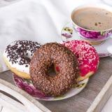 Donuts och kopp kaffe på wood bakgrund arkivfoto