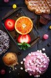 Donuts och muffin med frukt på svart stenar bakgrund royaltyfri bild