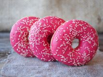 Donuts with pink frosting on the table. Donuts with pink frosting on a napkin made of burlap royalty free stock photo