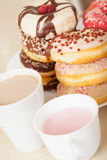 Donuts on  plate with cups Royalty Free Stock Images