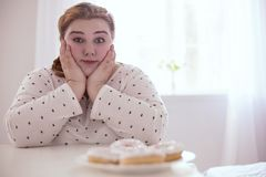 Charming young woman sitting next to donuts Stock Image