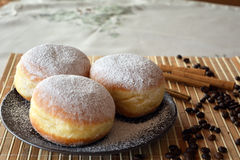 Donuts with powdered sugar on the brown plate on the table Royalty Free Stock Images