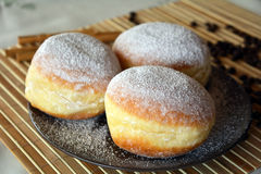 Donuts with powdered sugar on the brown plate on the table Royalty Free Stock Photos