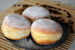 Donuts with powdered sugar on the brown plate on the table Royalty Free Stock Photo