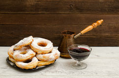 Donuts in powdered sugar, cezve of coffee and currant jam on a wooden background Royalty Free Stock Photos