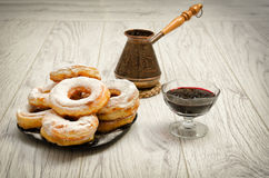 Donuts in powdered sugar, cezve of coffee and currant jam on a wooden background Stock Image