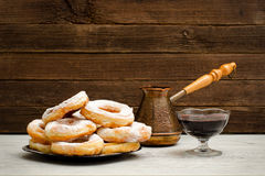 Donuts in powdered sugar, cezve of coffee and currant jam. Wooden background Royalty Free Stock Images