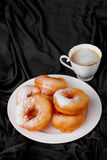 Donuts with powdered sugar and coffee on a black Stock Images