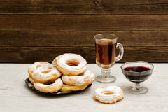Donuts in powdered sugar, a mug of tea and currant jam on a wooden background Stock Image