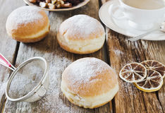 Donuts. With powdered sugar on a wooden background Stock Photos