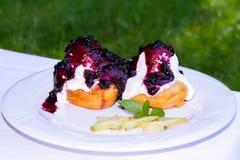 donuts, serowi bliny z czarnymi jagodami kumberland i śmietanka, słuzyć na białym talerzu Zdjęcia Royalty Free
